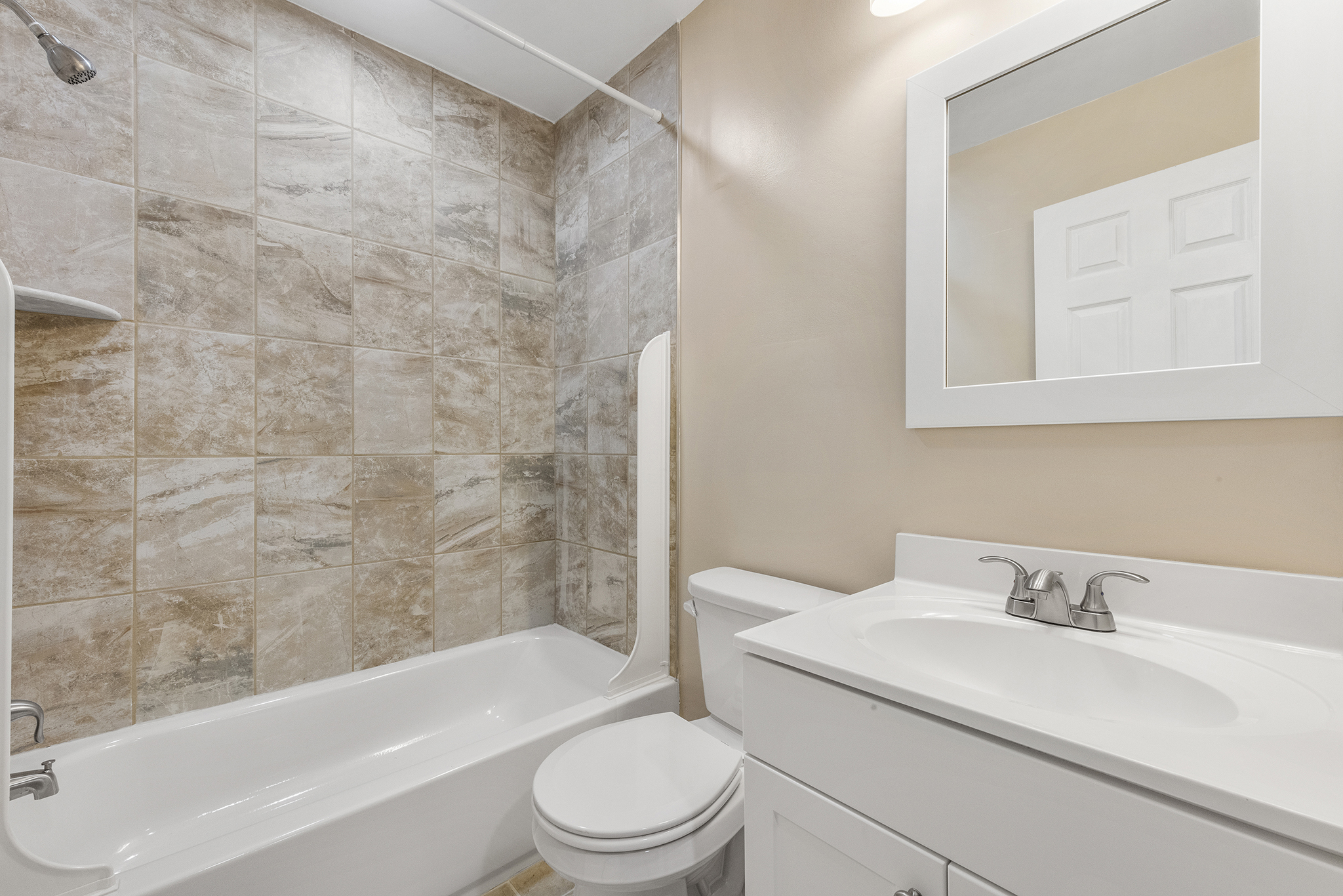 Gorgeous modern bathroom with a white sink and vanity and stone tiling in the shower